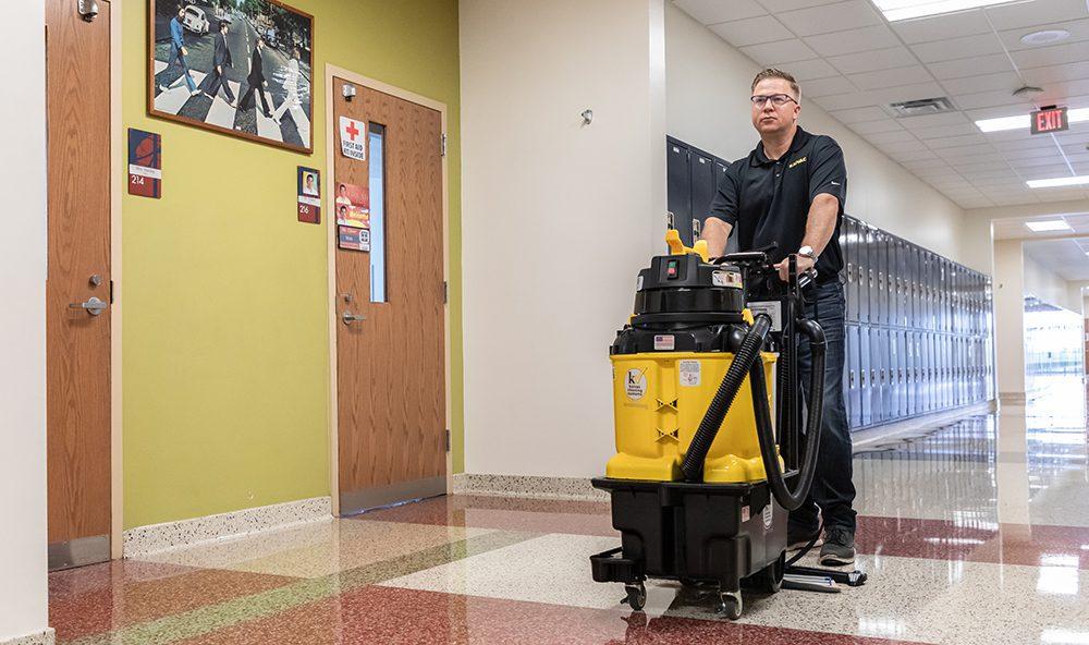 Kaivac AutoVac Stretch cleaning in a K-12 school hallway